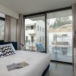 חדר שינה בדירות נופש עם שלושה חדרים שינה ומרפסת בשינקין